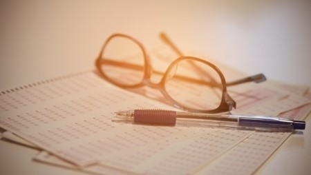 Test paper with glasses and pen