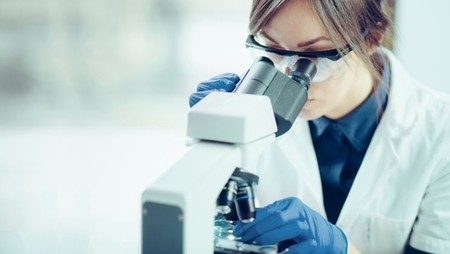 female forensic scientist using microscope