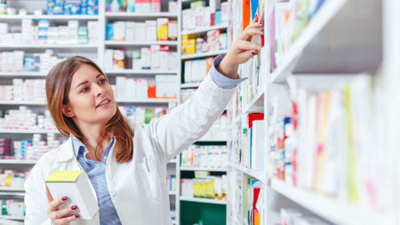 Pharmacist checking stock in an aisle of a local pharmacy