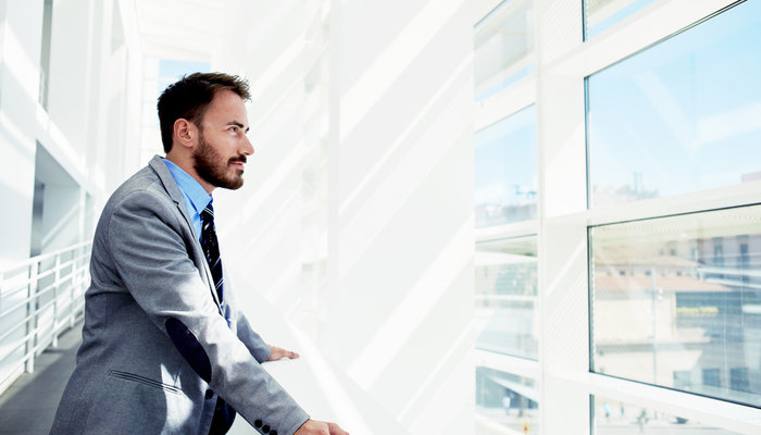 Confident businessman looking out window