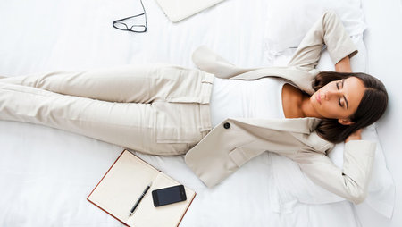 Businesswoman sleeping on bed