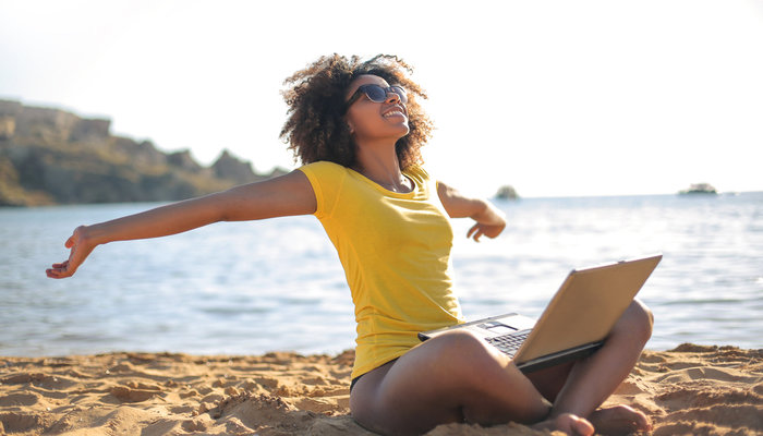 Young woman sitting on the beach and working on her laptop