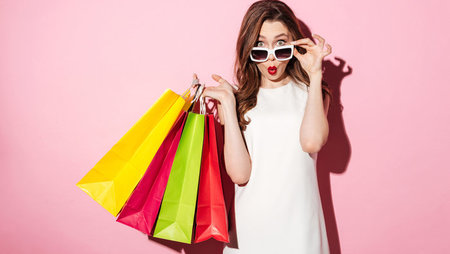 Young woman holding shopping bags and looking over sunglasses