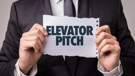 Closeup of businessman holding piece of paper saying 'elevator pitch'