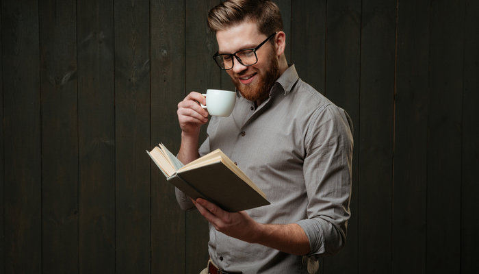 Smiling young man drinking coffee and reading book