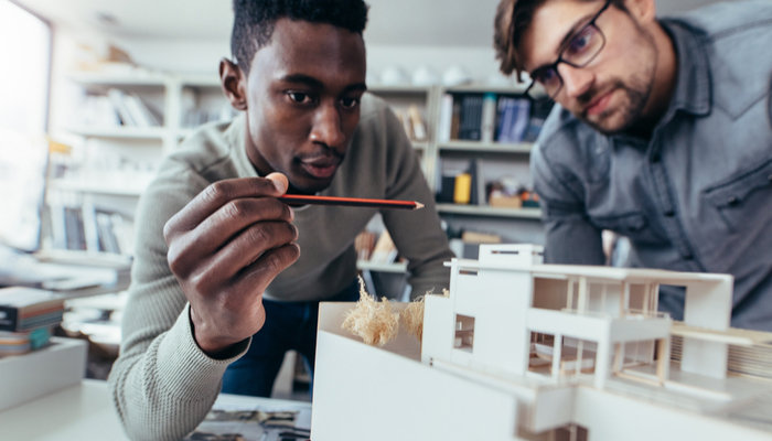 Two young architects inspecting house model