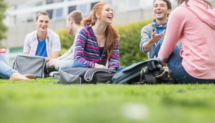 Group of university students sitting in park and laughing