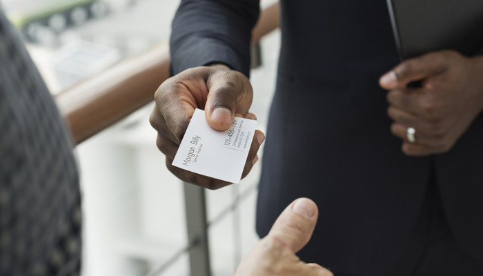 Closeup of businessman giving his business card to another businessman