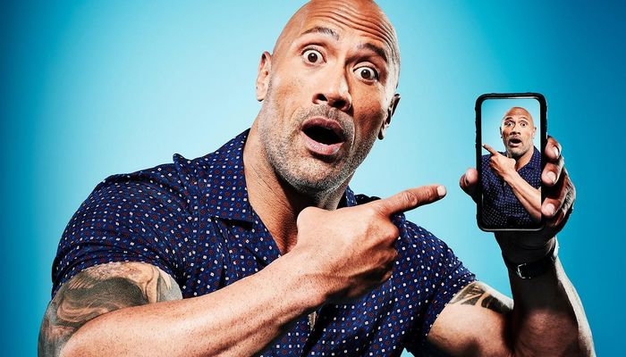 Dwayne 'The Rock' Johnson pointing at a photo of himself on a smartphone