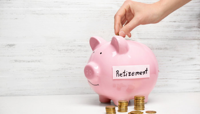 Close-up of a woman's hand putting a coin in a pink piggy bank with 'retirement' written on it