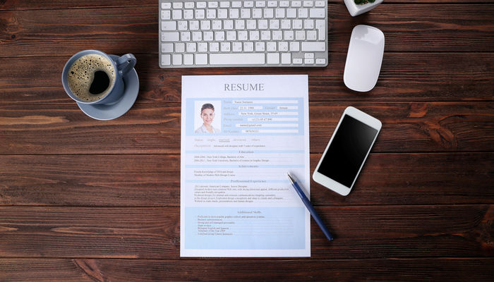 Résumé with a female candidate's photo on a desk with a keyboard and smartphone
