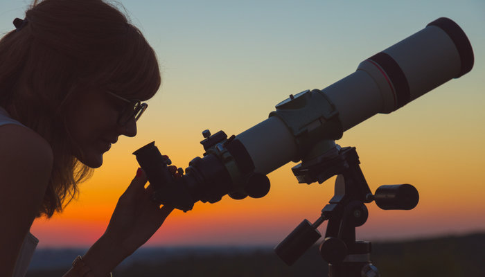 Woman looking at the sky through an astronomical telescope