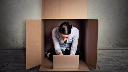 Young business woman working on a laptop in a large cardboard box
