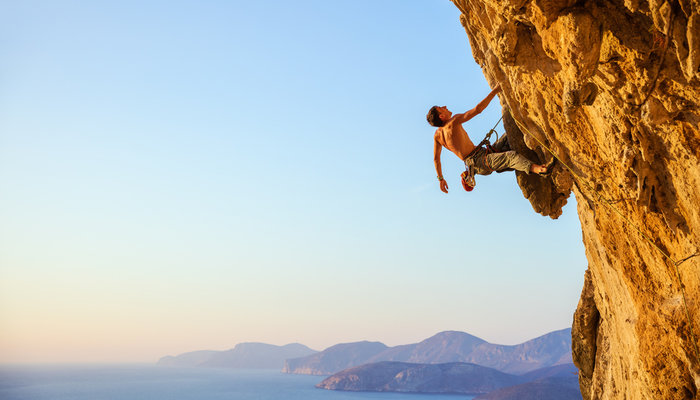 Young man climbing a rocky cliff