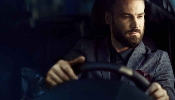 Close-up of a  handsome young businessman driving a car