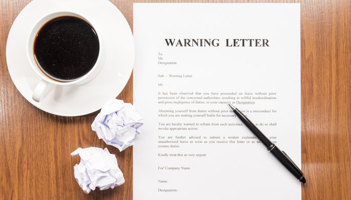 Top-down view of a warning letter and cup of coffee on a desk