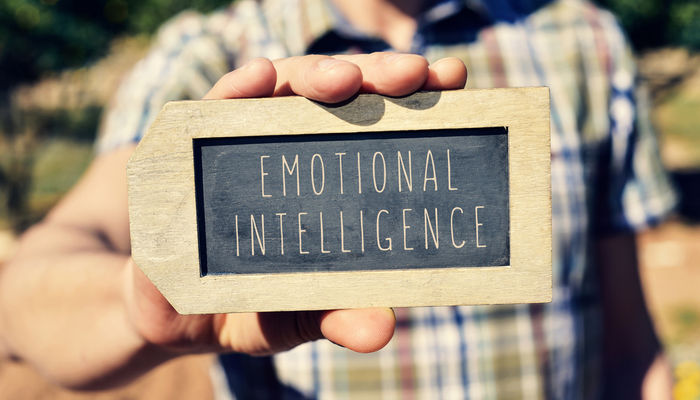 Close-up of a man holding a lapel-shaped chalkboard that has 'emotional intelligence' written on it