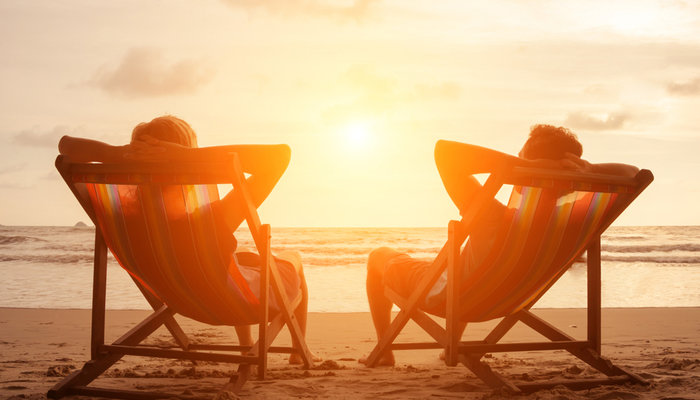 A young couple sitting in deck chairs on the beach and watching the sunset