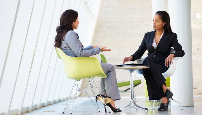 Two business women sitting around a table and talking