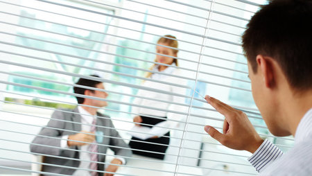 A manager watching two employees through window blinds
