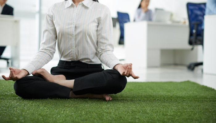 A businesswoman practising yoga in the office