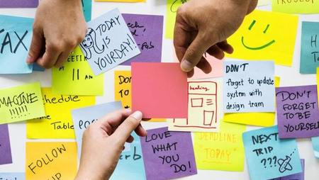 Close-up of hands holding sticky notes with motivational messages
