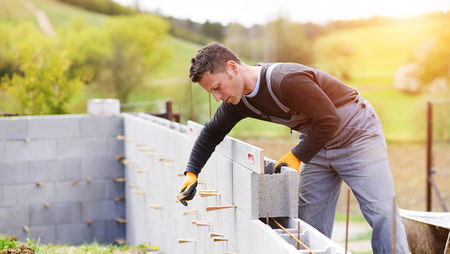 A young male bricklayer building a wall