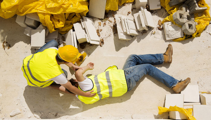 An injured construction lying on the ground and being tended to by a colleague after an accident