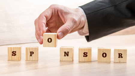 Close-up of a businessman's hand placing wooden block in a series of blocks to form the word 'sponsor'