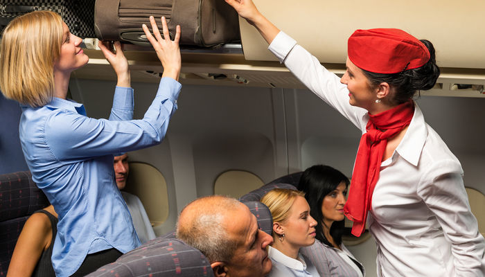 A female flight attendant helping a passenger with her luggage