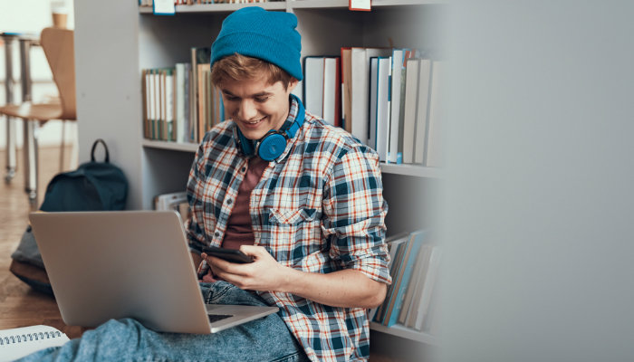 A happy student sitting on the library floor with his laptop, looking at his smartphone and wearing a pair of headphones around his neck