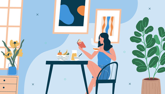 Illustration of a woman sitting by her kitchen table reading a book and having breakfast